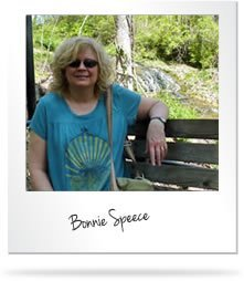 Bonnie Speece in sitting in a wood bench with nature background