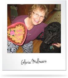 Gloria Mulhearn holding a heart shape cake with her black dog